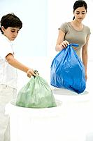 Young woman and boy placing garbage bags in separate garbage cans