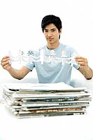 Young man with stacked newspapers, holding tree shapes cut out of paper, looking at camera