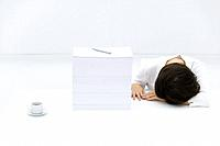 Woman with head down on desk, next to tall stack of papers