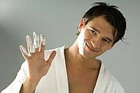 Man showing his hand with shaving cream on fingers, head tilted, smiling