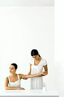 Woman receiving arm massage, looking away