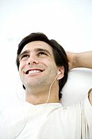 Man listening to earphones, smiling, one hand behind head
