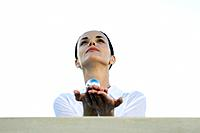 Woman holding yin yang balls in hands, low angle view