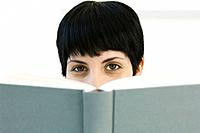 Woman peering over book at camera (thumbnail)
