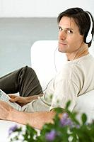 Man listening to headphones, looking over shoulder at camera, holding newspaper