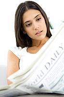 Woman reading newspaper, head tilted