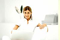 Woman sitting in armchair, holding laptop computer, smiling at camera