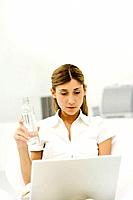 Woman using laptop computer, holding bottle of water