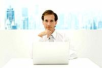 Businessman sitting in front of laptop computer, hand under chin, looking at camera