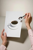 A woman holding a photograph of a coffee cup and a spoon