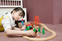 A girl playing with a train set