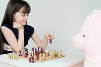 A girl playing chess with her teddy bear