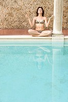 Woman meditating by swimming pool