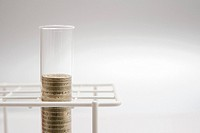 Pound coins in a test tube