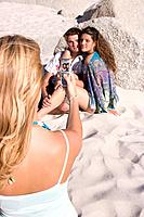 Young woman taking photograph with mobile phone of friends embracing on beach