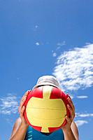 Man obscuring face with ball outdoors, low angle view