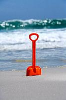 Red spade in sand on beach