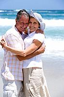 Mature couple embracing on beach, smiling, portrait of woman