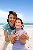 Mother embracing daughter 6-8 with camcorder on beach, smiling