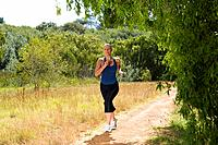 Woman running on country path, low angle view