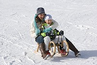 A mother and a daughter riding on a sledge