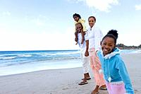Family of four walking on beach, portrait of girl 7-9 smiling, low angle view