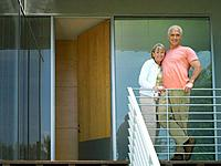 Senior couple arm in arm on balcony, smiling, portrait, low angle view