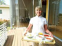 Mature woman with tray of food on decking, smiling, portrait