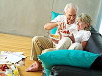 Mature couple eating breakfast on sofa, man pointing at woman's bowl, smiling, elevated view