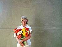 Mature woman with vase of flowers, smiling, portrait