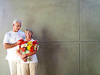 Mature man with hands on woman's shoulders, woman with vase of flowers, smiling, portrait