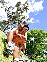 Young woman embracing young man in running clothes in park, smiling, portrait tilt