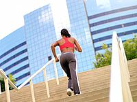 Woman running up stairs, rear view tilt