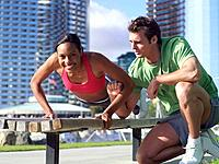 Male fitness instructor training woman on bench outdoors, smiling, portrait of woman