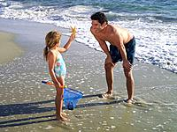 Girl 3-5 showing father starfish on beach