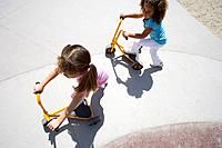 Girls 4-6 playing on tricycle scooters, elevated view