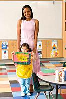 Nursery teacher by girl 3-5 with painting, smiling, portrait (thumbnail)