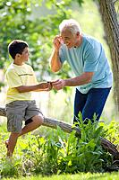 Boy 9-11 sharing MP3 player with grandfather outdoors