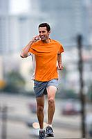 Man running outdoors, using mobile phone