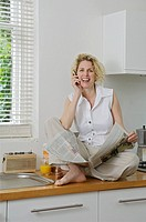 Woman on cellphone in kitchen