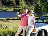 Couple on bonnet of car taking photograph of themselves by river