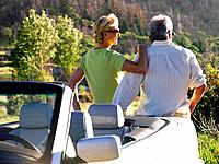 Couple by car looking at scenery, rear view