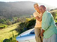 Mature couple by car in countryside, smiling, portrait