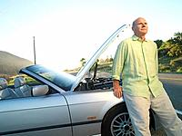 Senior man by broken down car on roadside
