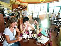 Young woman with friends in cafe, using mobile phones