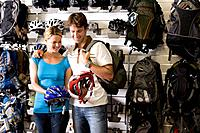 Young couple looking at bicycle helmets in shop (thumbnail)