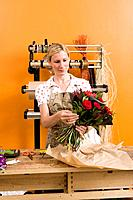 Female florist wrapping bouquet of flowers