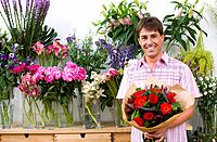 Male florist with bouquet of flowers, smiling, portrait