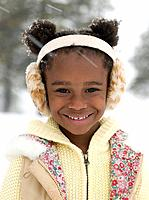 African girl with ear muffs in the snow