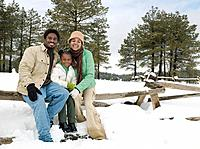 African family sitting on snowy wooden fence